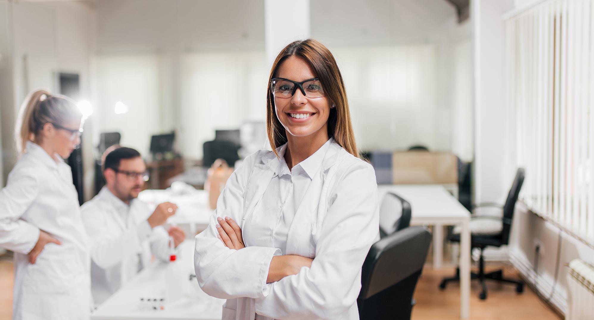 Woman with arms crossed in a lab wearing safety glasses