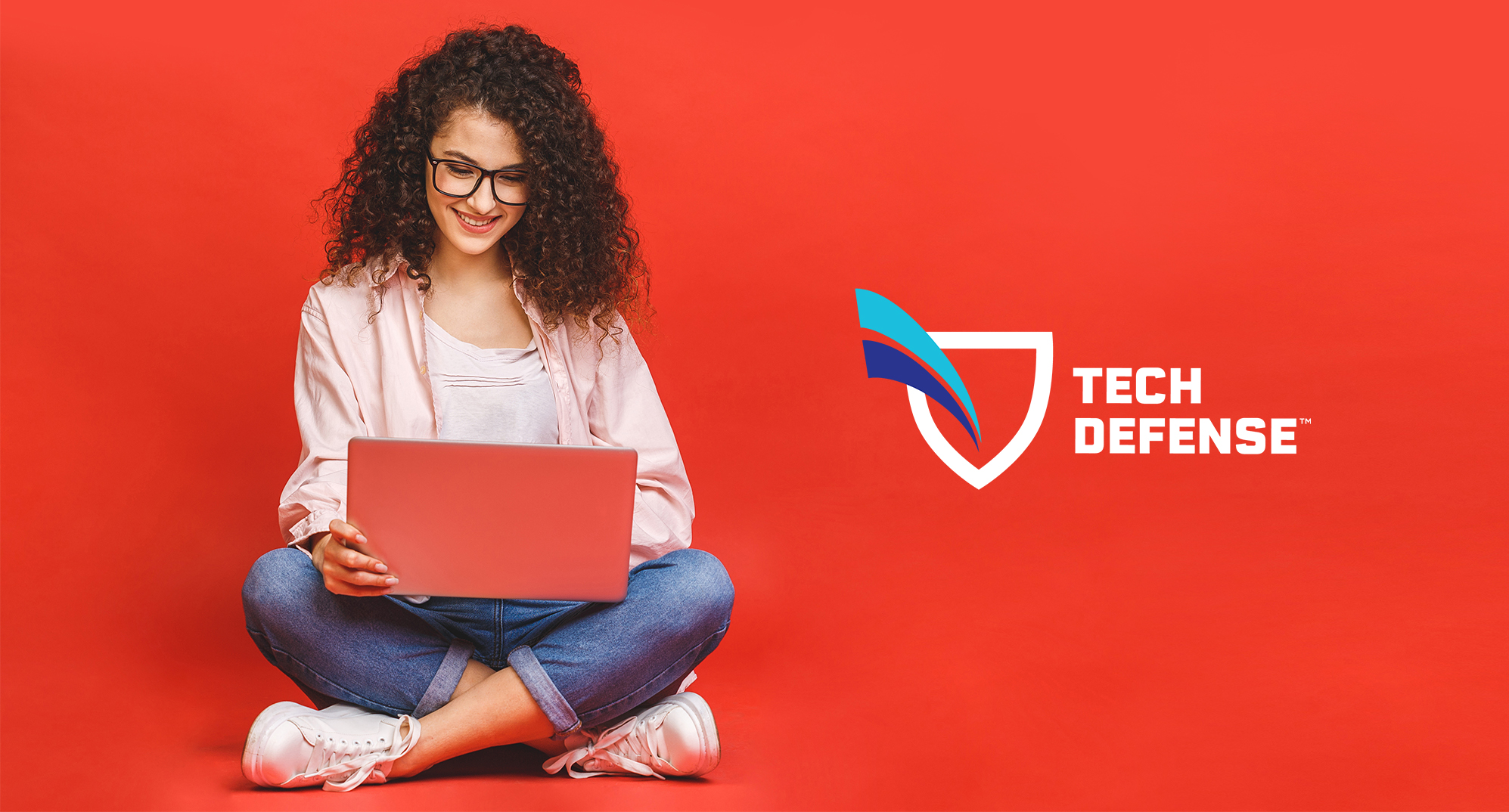 Woman on laptop with the Tech Defense logo™