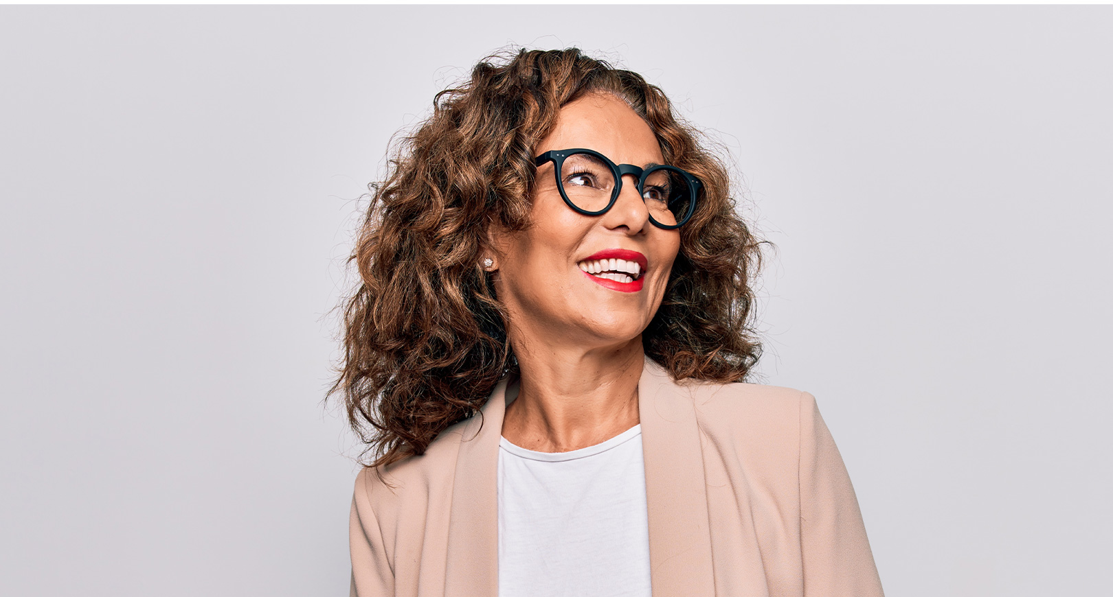 smiling woman wearing glasses gazing into the distance
