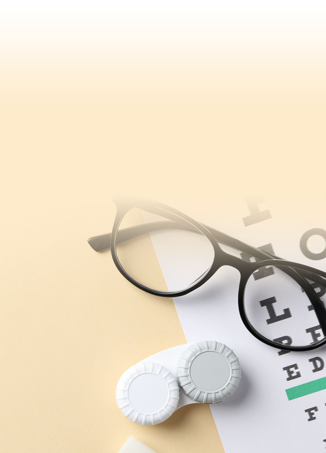 eyeglasses and contact lenses on top of an eye chart