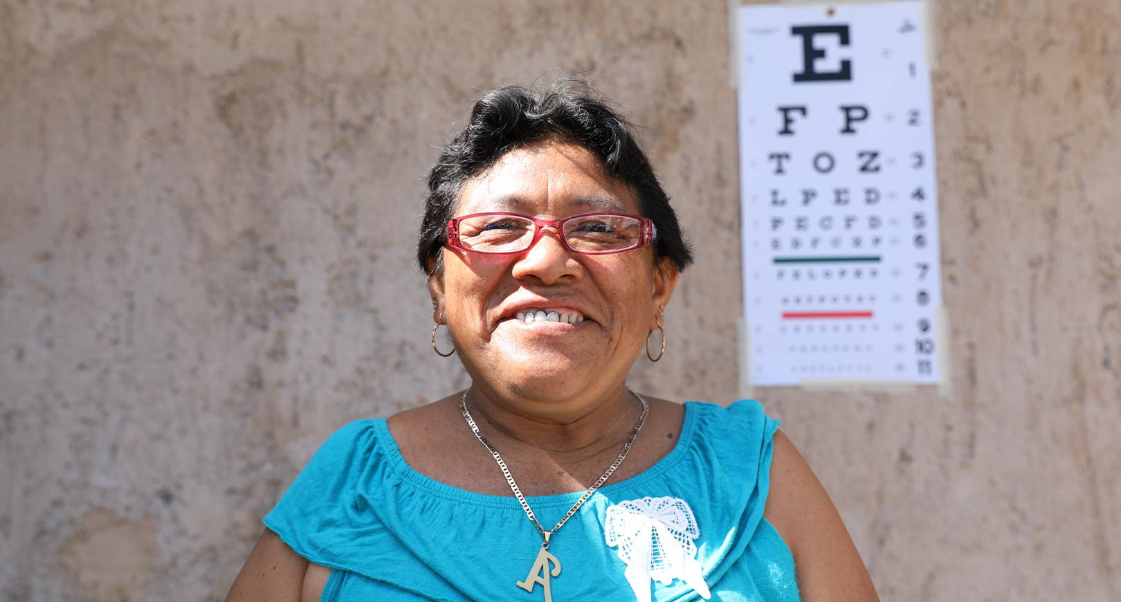 laughing woman standing in front of eye chart